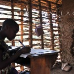 Students work in classrooms that are often falling apart. This school is located on the side of a mountain and the mud walls have been eroded away.