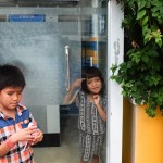 Children grow up on the streets where their parents work. These children play in an ATM booth.