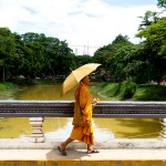 A monk walks on a bridge over the Siem Reap River.